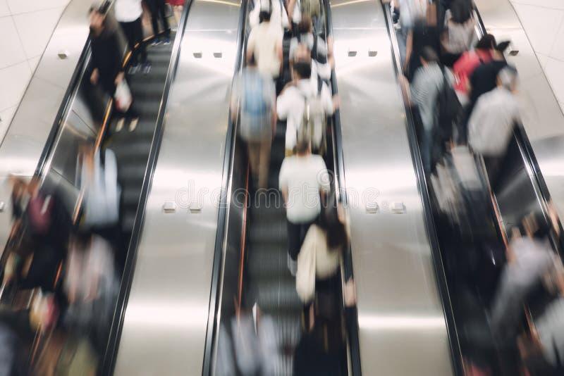 步行者、薪水工作者在旅行的自动自动扶梯上下到工作和回家 免版税库存照片