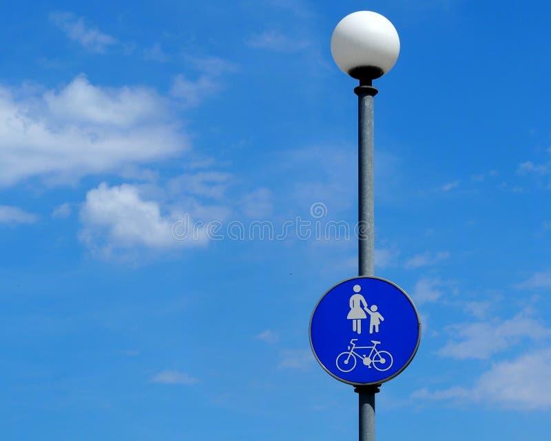 步行者和骑自行车者区域标志 与母亲、孩子和自行车剪影的蓝色路标在街灯 免版税库存照片