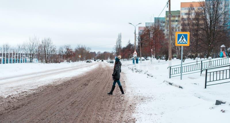 步行者在冬天穿过路在一条积雪的路的城市,轮子踪影在雪的在a的城市 库存图片