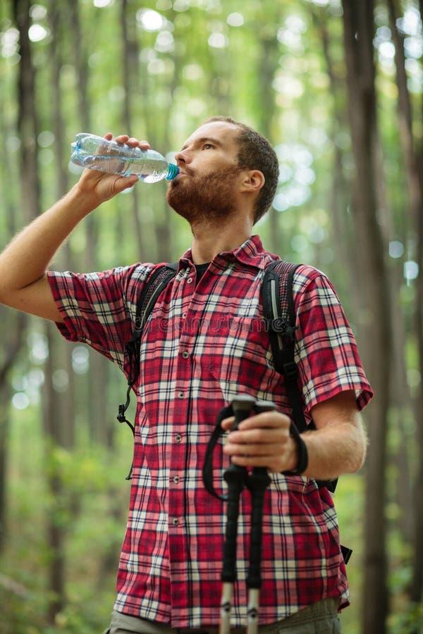 步行通过森林,饮用水和休息的坚定的年轻人 免版税库存照片