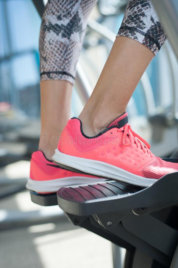 步进使用的妇女的特写镜头和训练在健身俱乐部 免版税库存照片