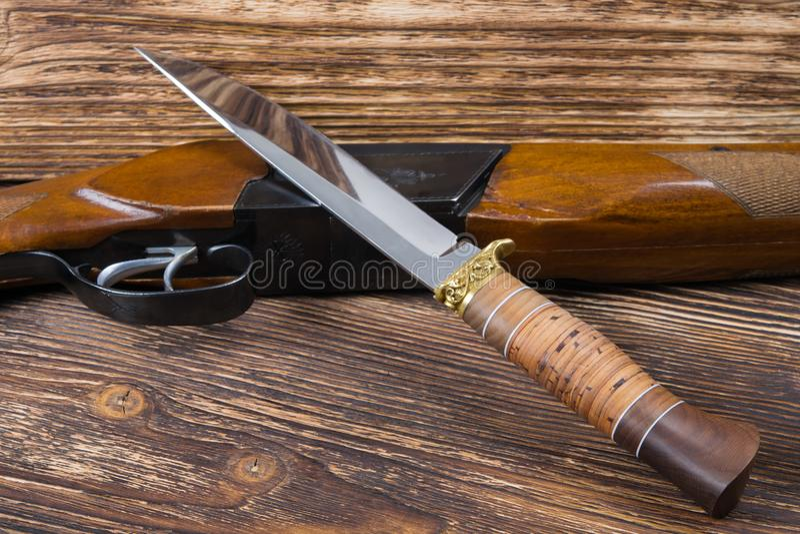 武器和一起猎刀在木背景 图库摄影