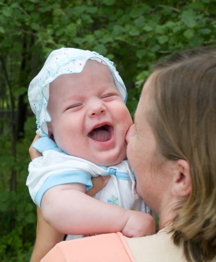 武装婴孩笑的母亲 库存照片
