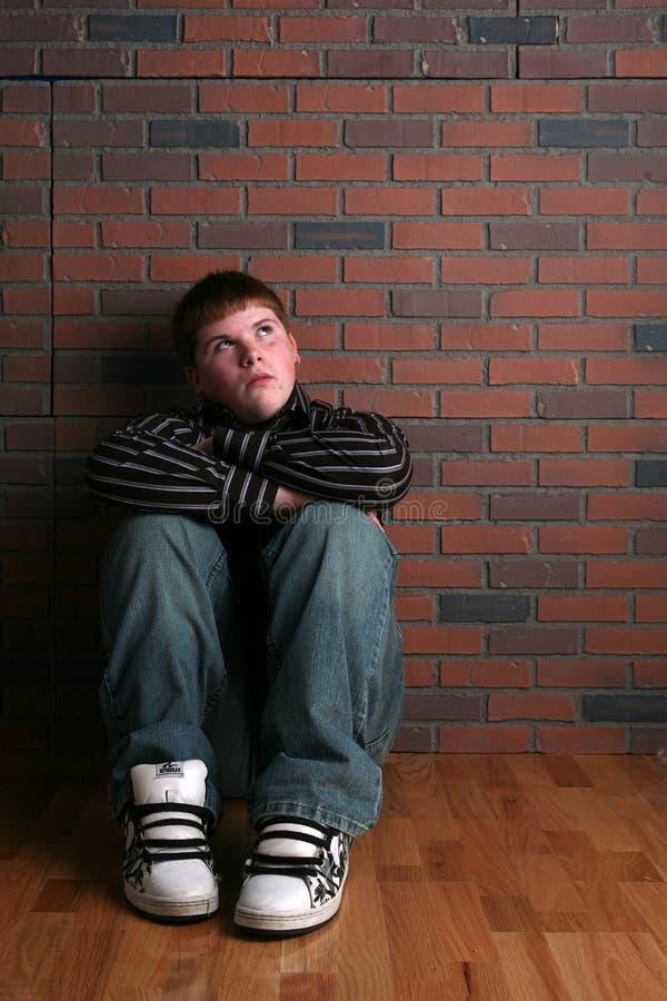 武装男孩楼层膝盖坐少年 免版税库存照片