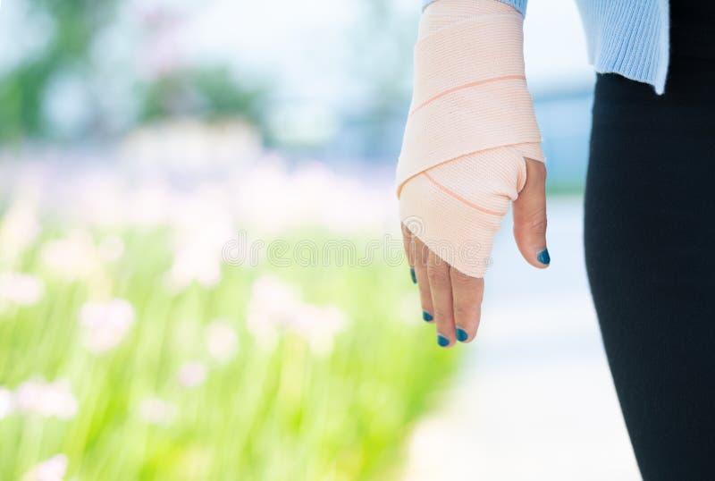 武装藤条,有下体的受伤的女性手 有有弹性织品的手绷带 免版税库存图片