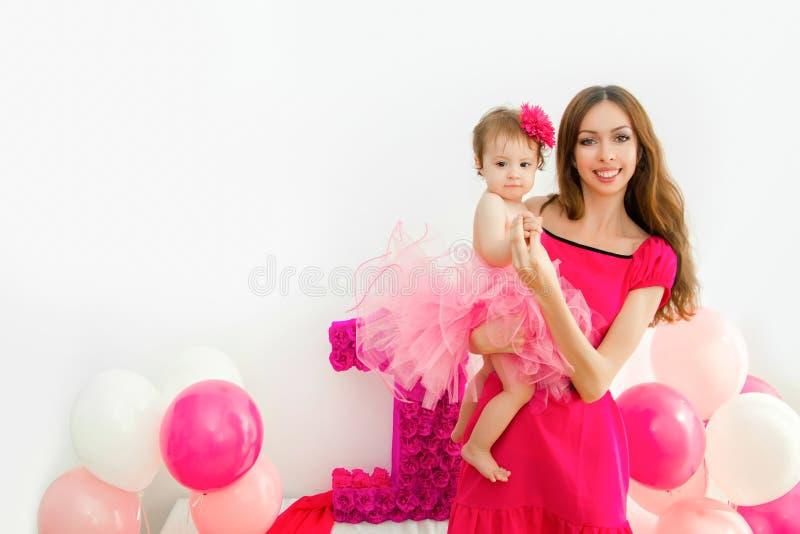 武装婴孩她的藏品母亲 一条桃红色裙子的小女孩 库存照片