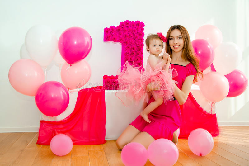 武装婴孩她的藏品母亲 一条桃红色裙子的小女孩 免版税库存图片