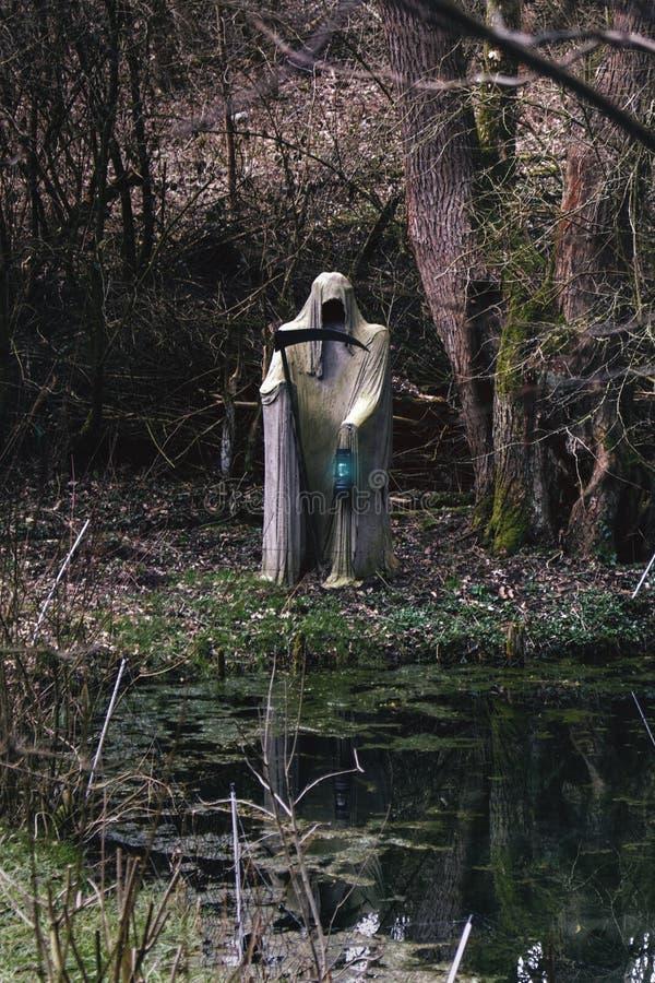 死亡的白收割机与鬼的大镰刀和灯的在一个小池塘 免版税库存照片