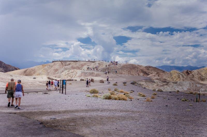 死亡谷,加利福尼亚:游人走到Zabriskie点,风景在热的国立公园俯视 库存图片