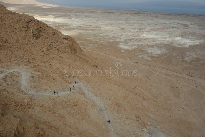 死海在显示供徒步旅行的小道的冬天期间由马萨达决定 库存图片