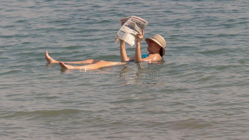 死海,以色列- 2016年9月,22日:读报纸的妇女,当漂浮在以色列的死海时 图库摄影