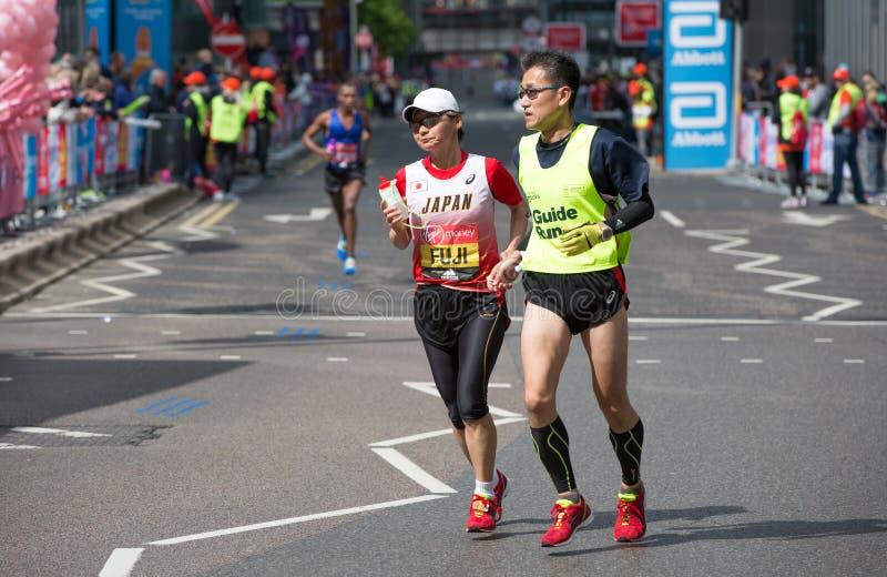 残疾与指南赛跑者的运动员连续距离在金丝雀码头 伦敦 免版税图库摄影