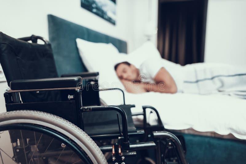 残疾人在黑轮椅附近睡觉 免版税库存图片