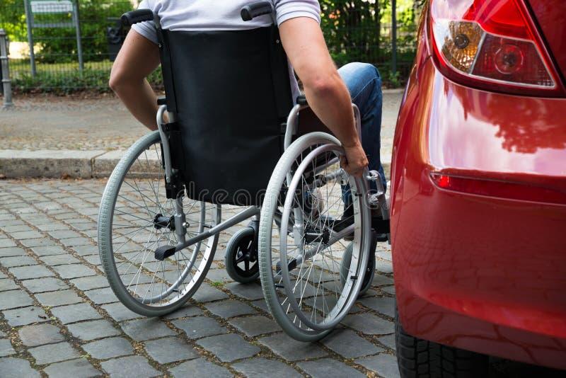 残疾人坐轮椅在他的汽车附近 库存照片