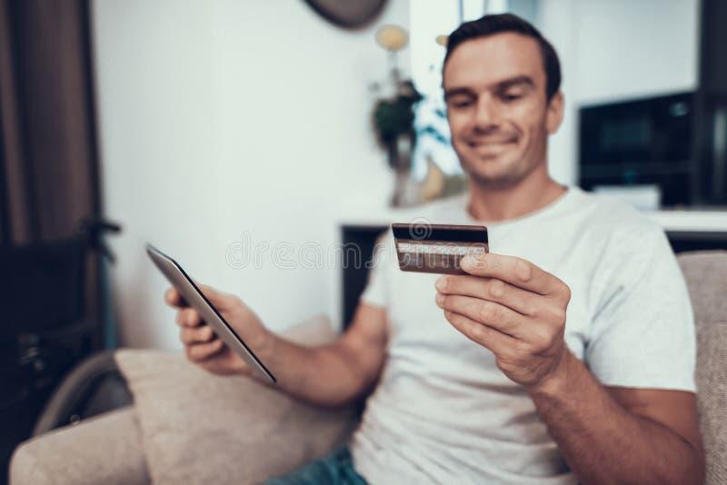 残疾人拿着信用卡并且使用片剂 免版税图库摄影