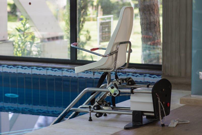 残疾人的升降椅设备接近的游泳池的 库存图片