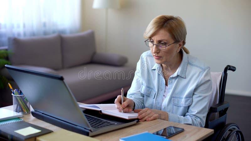 残疾在笔记本,冲浪的互联网的祖母文字新的烹调食谱 免版税库存照片