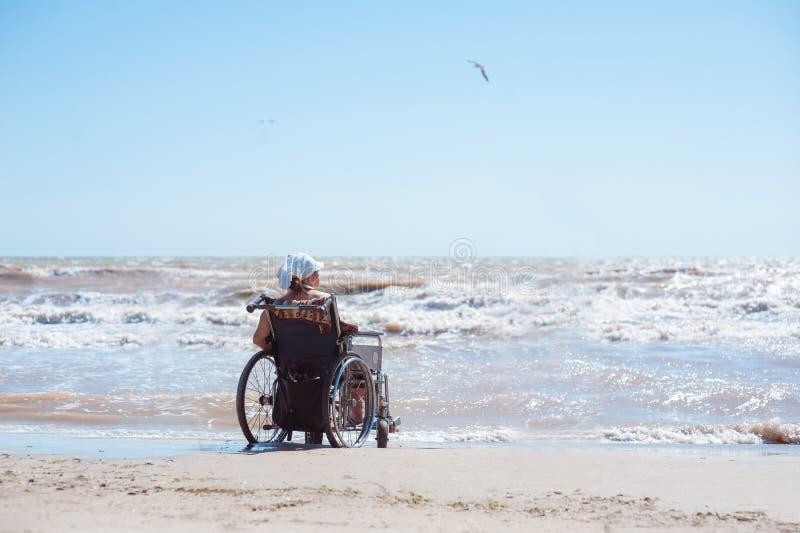 残疾妇女的背面图坐在海滩的一个轮椅在一好日子 她看海洋 免版税库存图片