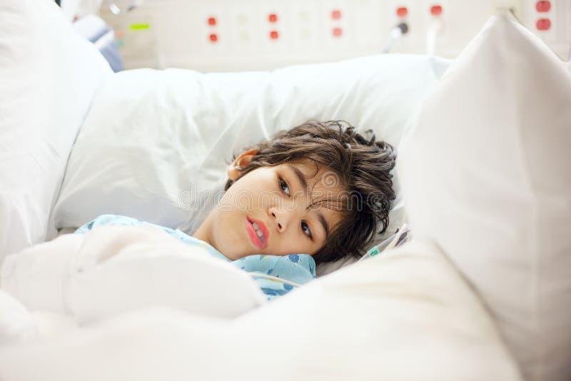 残疾小男孩说谎的病残在医院病床上 库存照片