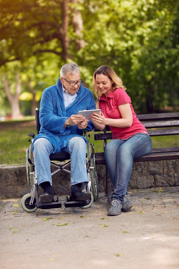 残疾退休人员人在使用片剂的公园有女儿的 免版税库存照片