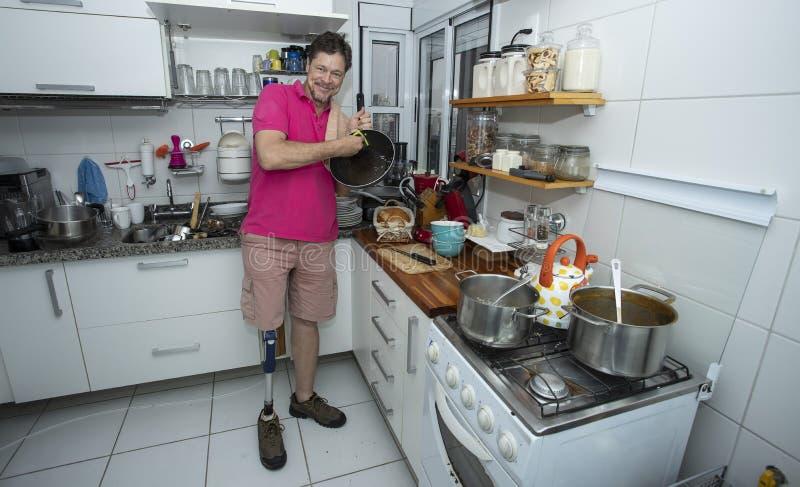 残疾 没有腿的人 清洗厨房 免版税库存图片
