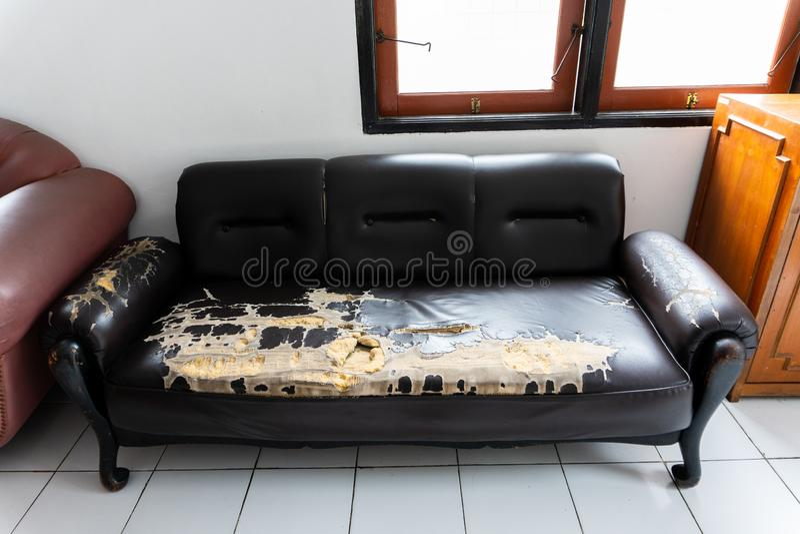 残破和老棕色长沙发椅子 免版税库存照片