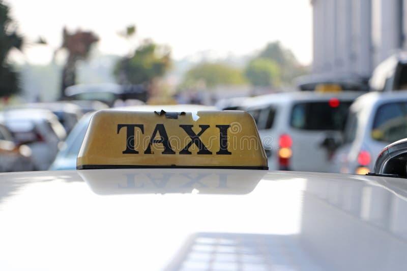 残破的出租汽车光标志或小室在与黑文本的土褐色的黄色颜色签字在汽车屋顶在街道被弄脏的背景 免版税库存图片