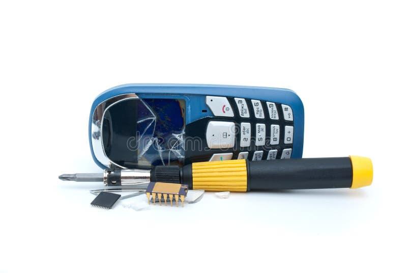 残破的微芯片移动电话螺丝刀 免版税库存照片
