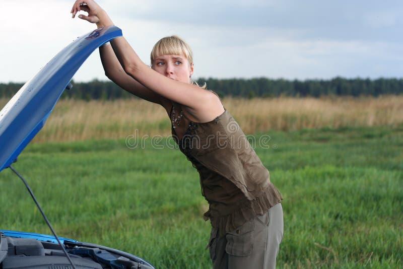 残破的汽车她的妇女年轻人 免版税库存图片