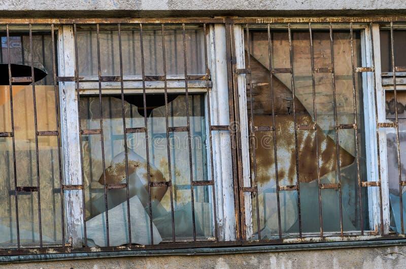 残破的窗口关在监牢里在一个老被放弃的房子里 免版税图库摄影