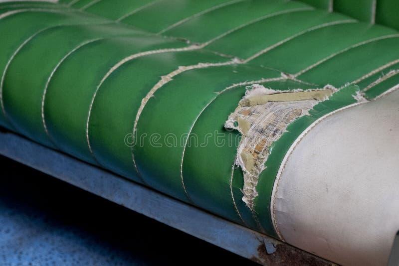 残破的绿色皮革沙发 库存照片