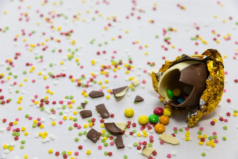 残破的金黄巧克力复活节彩蛋用五颜六色的巧克力里面在与五颜六色的被弄脏的五彩纸屑的白色背景 免版税库存图片
