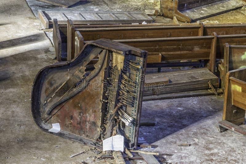 残破的钢琴在一个被放弃的教会里 免版税库存图片
