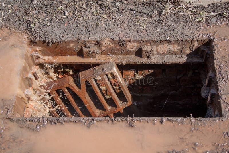 残破的风暴流失 肮脏的水,在雨和垃圾进入天沟后 免版税库存照片