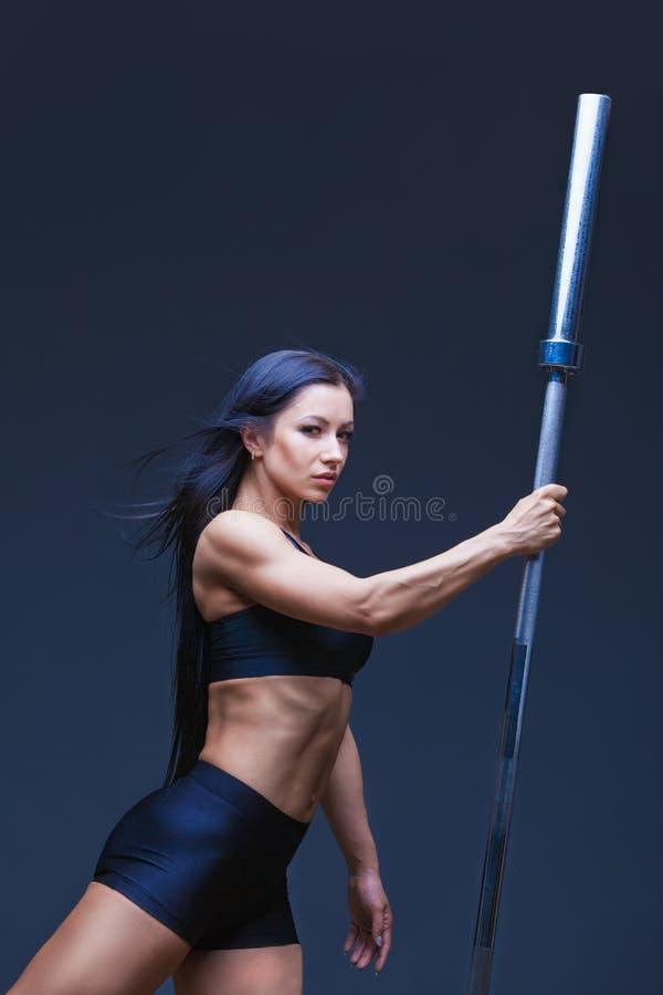 残酷运动性感的妇女拿着杠铃 锻炼的概念炫耀,给健身房做广告 隔绝在黑色 免版税库存照片