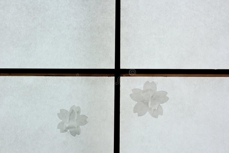 残破的日本扯窗滚滑门修理与樱花补丁 免版税图库摄影