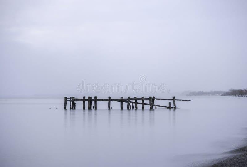 残破的码头岗位在镇静平静的水,有薄雾的有雾的蓝色backg中 免版税图库摄影