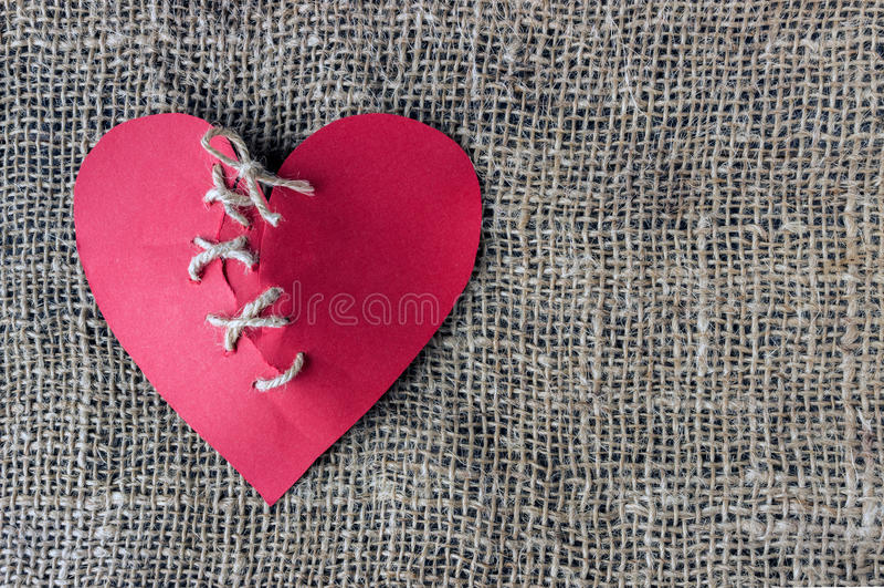 残破的红色心脏 被缝合的螺纹 离婚, separat的概念 库存图片