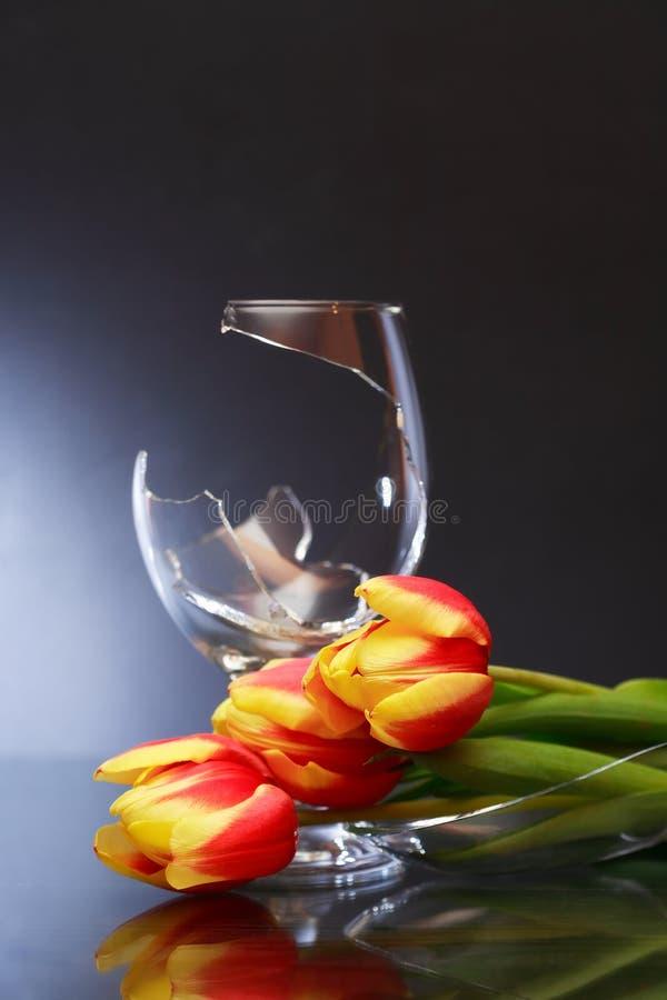 残破的葡萄酒杯和花 免版税库存图片