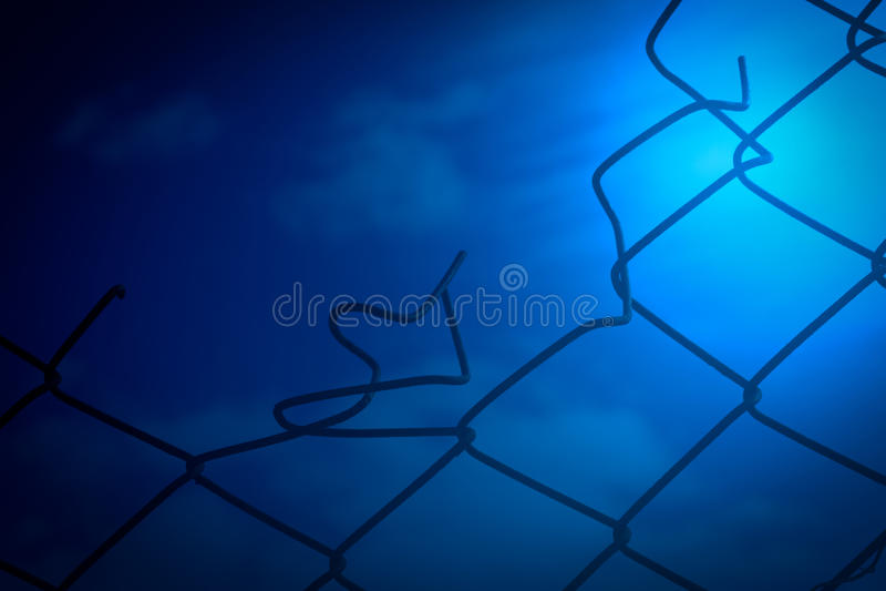 残破的铁丝网和蓝天背景 免版税库存图片