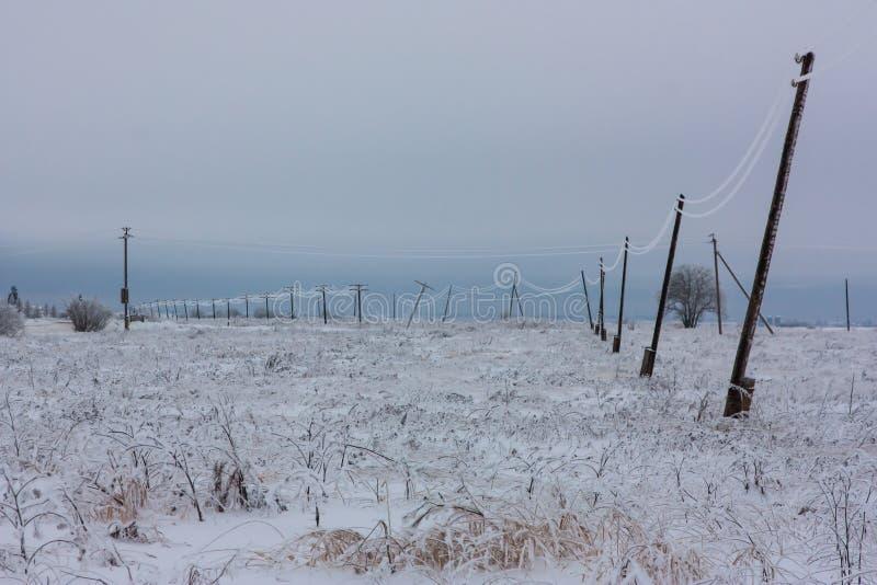 残破的阶段电能标示用在木电杆的树冰在乡下在风暴以后的冬天 免版税图库摄影