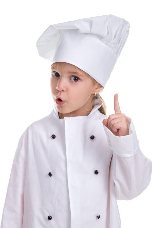 殷勤在白色背景隔绝的女孩厨师白色制服,看直接与一个指向的手指的照相机 免版税图库摄影