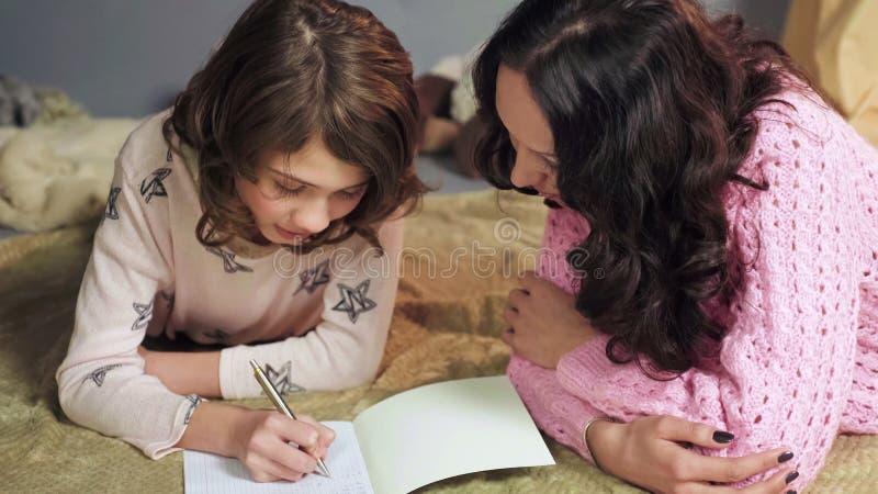 殷勤地做家庭作业,母亲监视差错,家庭教育的女儿 免版税库存图片