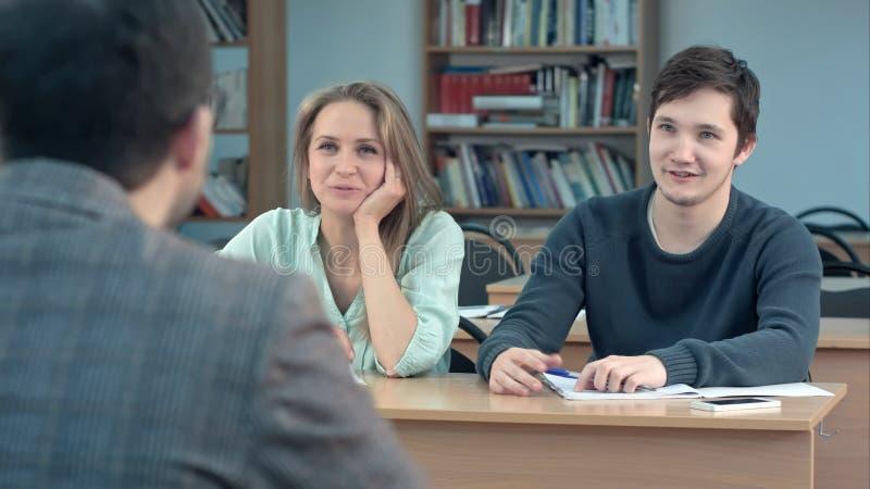 殷勤地听男老师和沟通在教室的学生 免版税库存照片