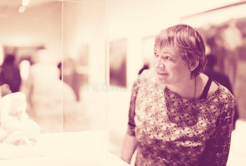 殷勤地看雕塑的退休人员妇女画象 免版税库存照片