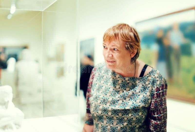 殷勤地看雕塑的退休人员妇女画象 库存照片