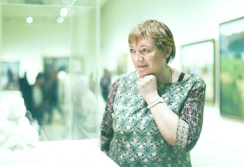 殷勤地看雕塑的退休人员妇女画象 免版税图库摄影