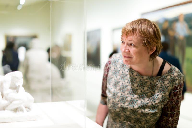 殷勤地看雕塑的退休人员妇女画象 免版税库存图片