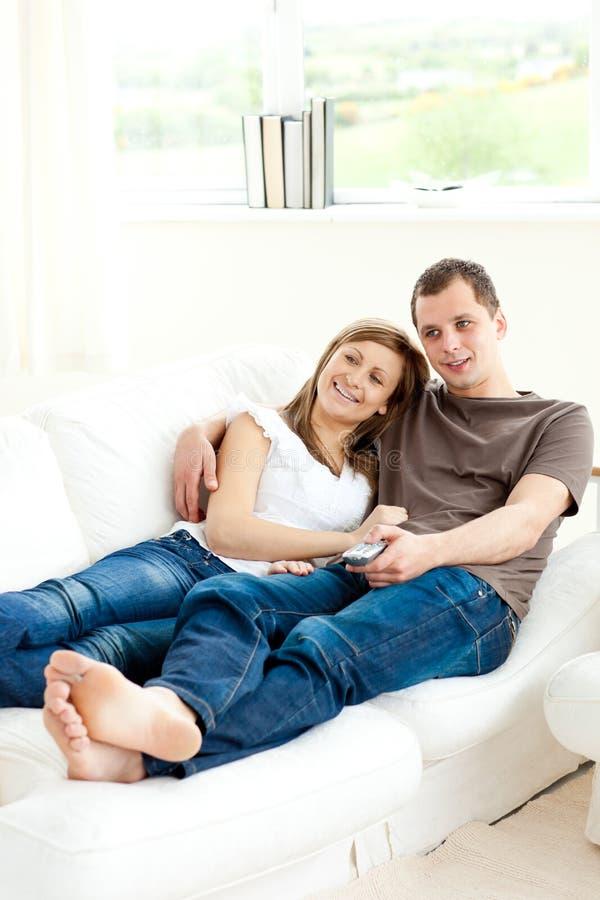 殷勤夫妇沙发电视注意的年轻人 免版税库存图片