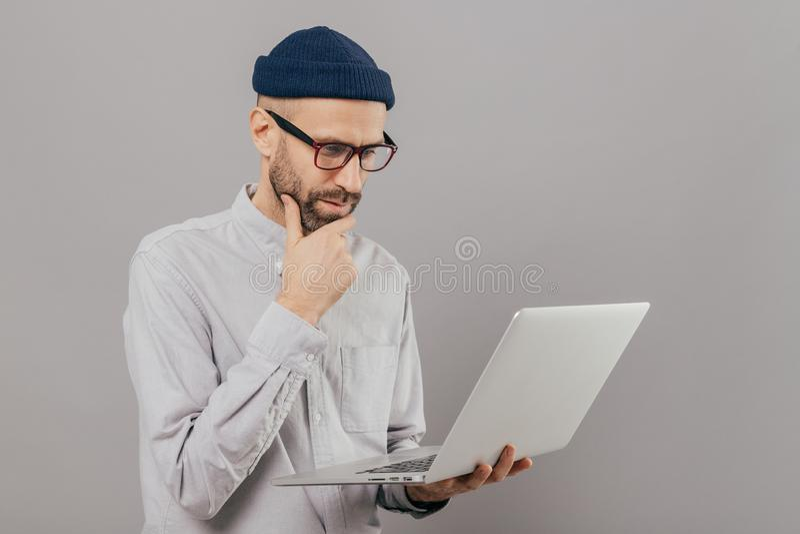 殷勤学生握下巴,聚焦在手提电脑显示器,搜寻信息项目,被连接到无线 免版税库存照片